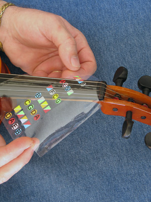 Step 2 slide the violin fingering guide over the fingerboard and under the strings